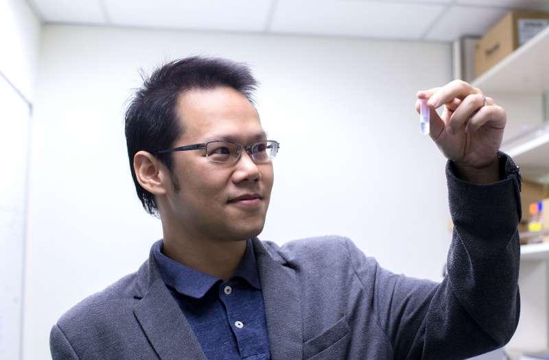 胡哲銘看著自己發明的冠狀病毒奈米疫苗,小小的容器裡充滿了 10000000000000 個薄殼中空奈米粒子(圖/研之有物)