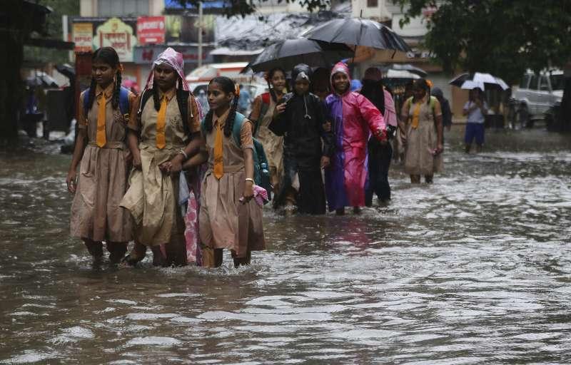 南亞季風暴雨引起水災,印度孟買學童涉水通行。(美聯社)
