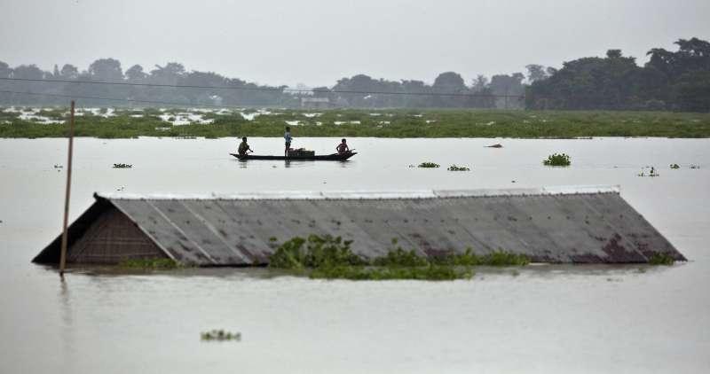 季風降雨導致南亞嚴重水災。印度阿薩姆邦最大城古瓦哈提(Guwahati)房舍幾乎沒頂,居民乘小船移動。(美聯社)