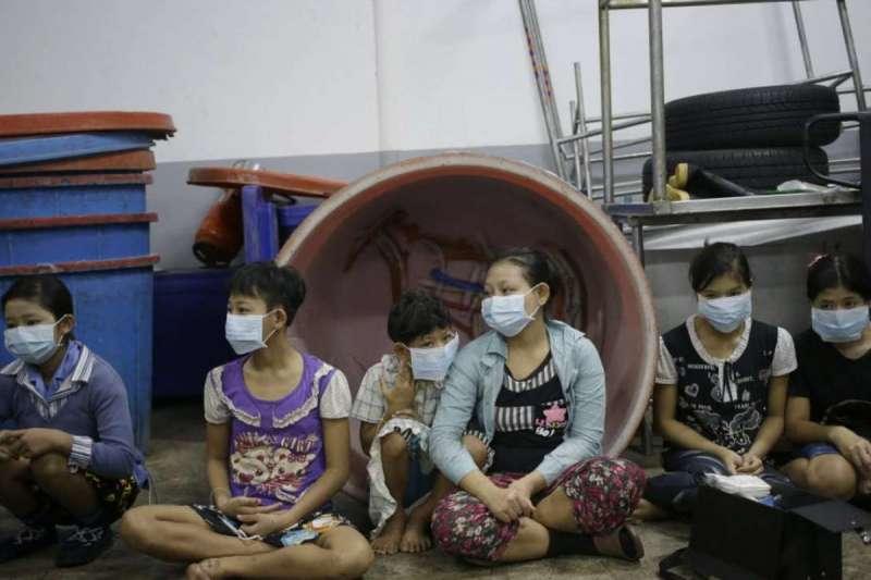 泰國中部龍仔厝府一家蝦子工廠,在工廠工作的兒童與青少年坐在地上,等待臨檢的警方登記(美聯社)