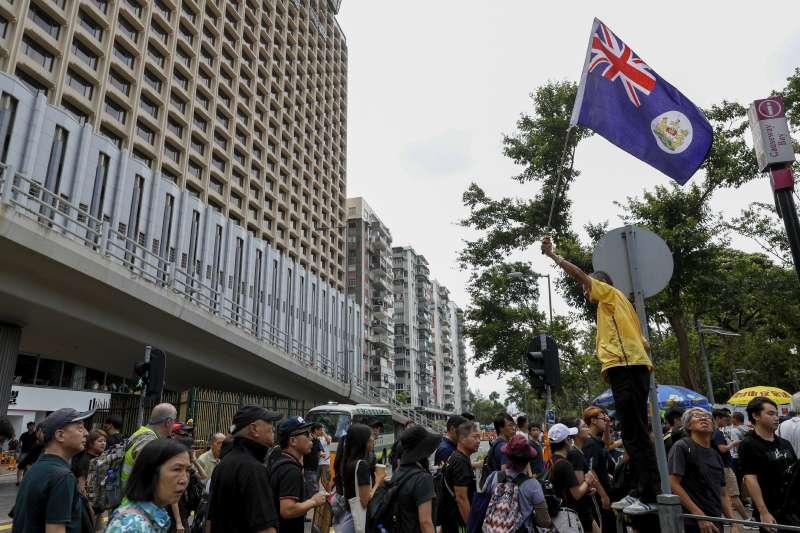 部分反送中民眾在遊行中揮舞港英旗。(美聯社)