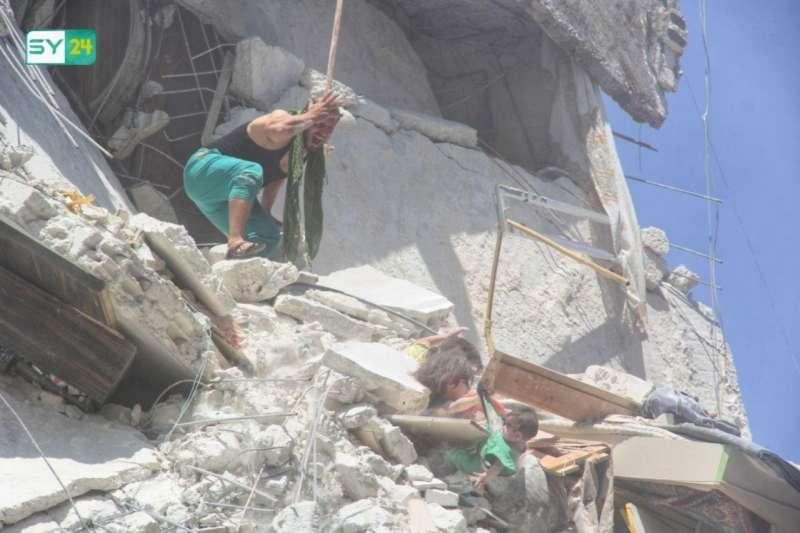 2019年7月24日,敘利亞伊德利卜省遭到政府軍空襲,陷在瓦礫堆中的5歲女童莉涵伸出右手,揪著就要墜入瓦礫堆下妹妹的衣服。(取自敘利亞新聞網站SY24,www.sy-24.com)
