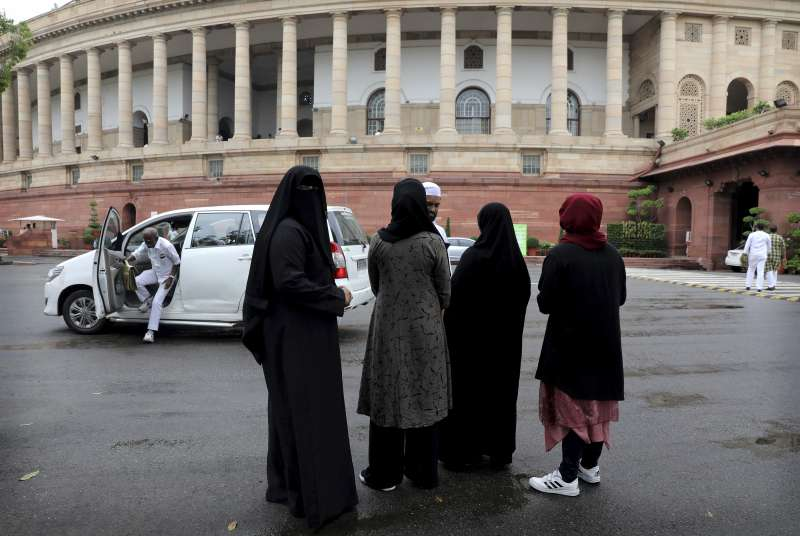 印度下議院上星期通過法案,禁止說3次「休妻」離婚的穆斯林習俗,一些穆斯林婦女站在新德里的國會外等待投票結果(美聯社)