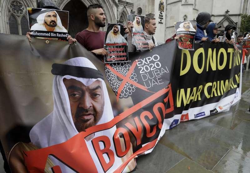 杜拜酋長穆罕默德與王妃哈雅公主的離婚訴訟於英國高等法院開打,法院外不滿穆罕默德的群眾舉布條示威。(美聯社)