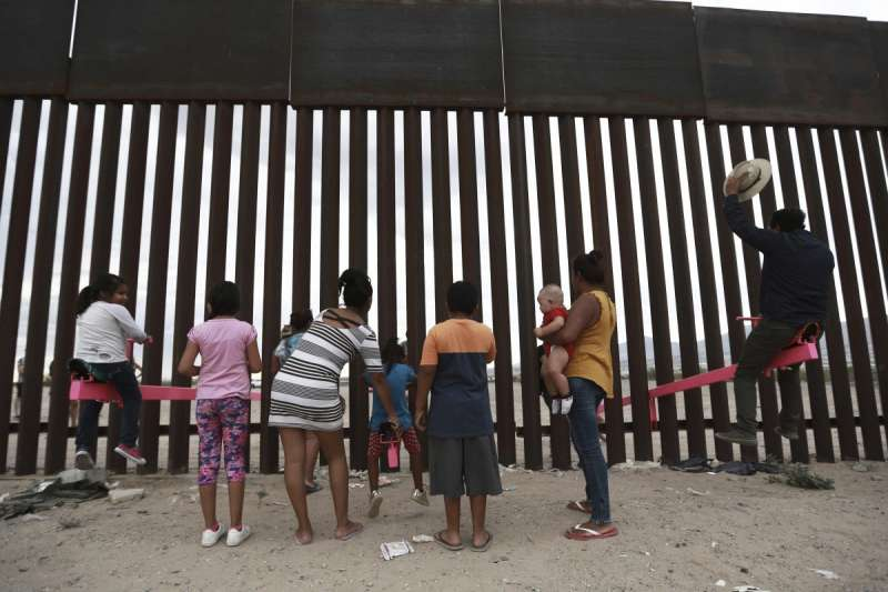 兩位教授在美墨邊境高牆設立「邊境翹翹板」,兩邊的大人小ˋ孩玩得不亦樂乎。(AP)