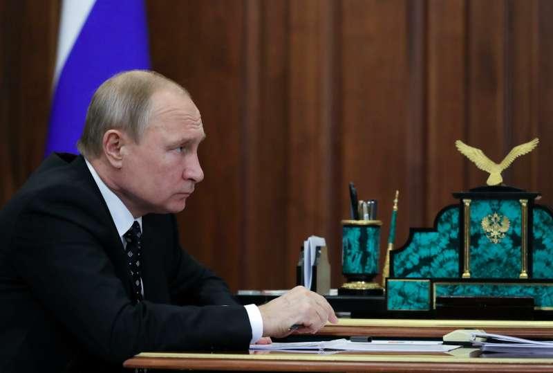 俄羅斯總統普京,1日專注聽取官員報告。(AP)