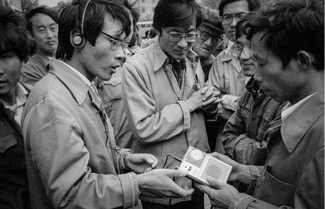 一個隨身攜帶的收音機引起眾人圍觀。上海(1985年)。(BBC中文網)