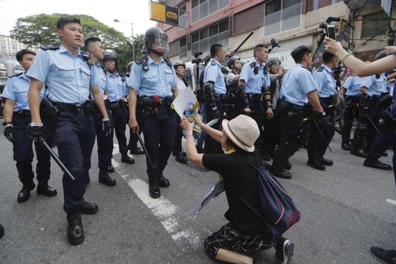 7月31日,一名香港民眾跪地懇求香港警察不要攻擊示威者(美聯社)