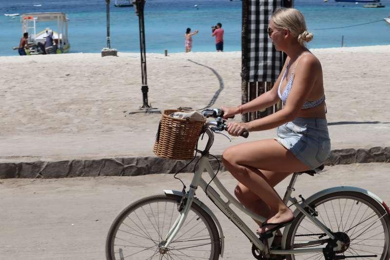 印尼吉利群島禁止汽機車進入,德拉望安島上騎自行車漫遊的外國旅客。(蔡娪嫣攝)