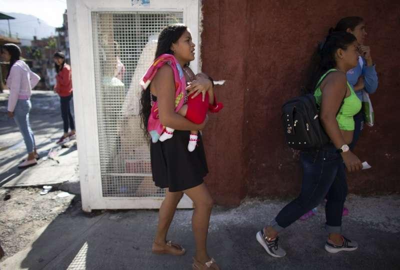 15歲的委內瑞拉小媽媽拉米雷茲抱著女兒,前往診所排隊,嘗試獲得皮下避孕器。(AP)