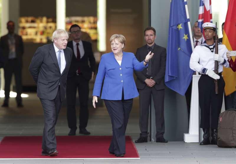 英國首相強森(左)與德國首相梅克爾(右)21日在德國會面(美聯社)
