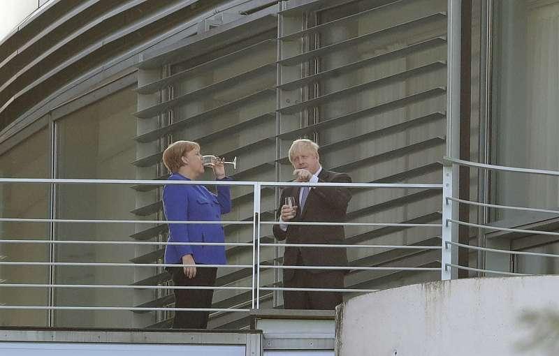 英國首相強森與德國首相梅克爾21日在德國會面(美聯社)