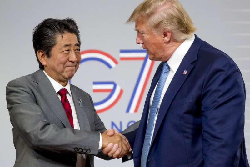 日本首相安倍晉三和美國總統川普8月25日在日美峰會上相互握手致意。(美聯社)