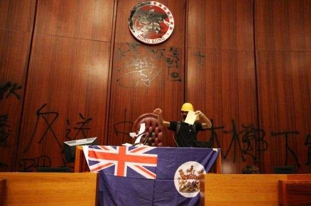 示威者在香港立法會會議廳塗污區徽,展示港英旗幟。(BBC中文網)