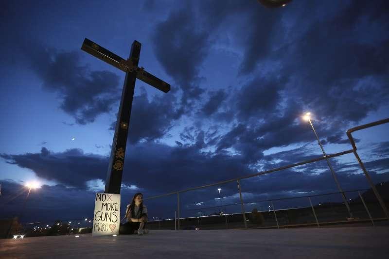 8月3日美國德州帕索發生大規模槍擊案,一名女子坐在控訴槍枝暴力氾濫的標語旁悼念。(美聯社)