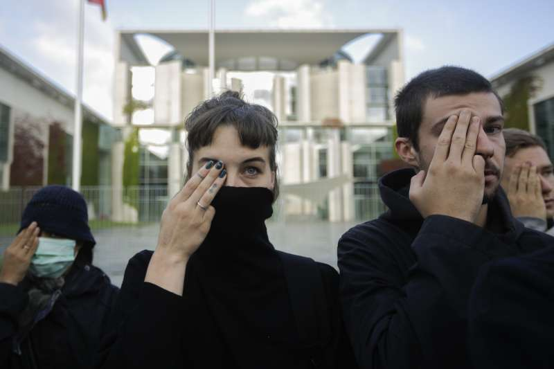 德國民眾在柏林呼籲政府關注香港反送中運動人權問題,擺出「警察還眼」手勢。(AP)