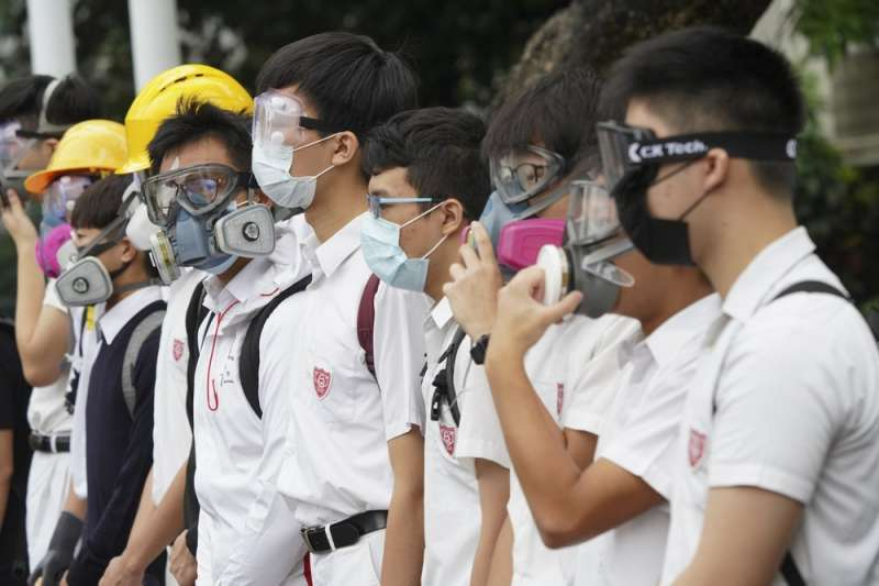 香港「反送中」運動,中學生牽起人鍊,不忘戴上防毒面具或口罩象徵抵抗警察暴力。(AP)