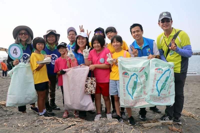 師生翻越中芸海堤進入沙灘,每組都有大型布袋、環保紙袋與鐵夾,學生們也戴上手套防止受傷,在日頭下開始進行淨灘。(圖/徐炳文攝)