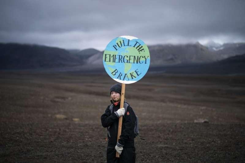 冰島今年7月將「OK冰川」除名,參加冰川喪禮的少女舉起「踩下緊急煞車」標語。(美聯社)