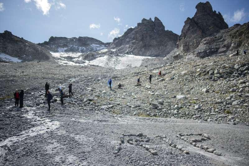 瑞士民眾在地上用碎石排出RIP字樣。(美聯社)