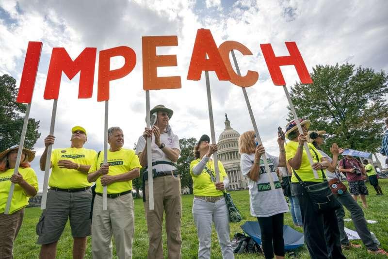 反對川普的美國民眾在國會山莊旁高舉「彈劾」(IMPEACH)的標語,以示抗議。(美聯社)