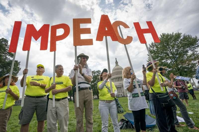 美國總統川普因為「烏克蘭門」疑似濫用職權打擊政治對手,圖為呼籲彈劾川普的民眾。(AP)