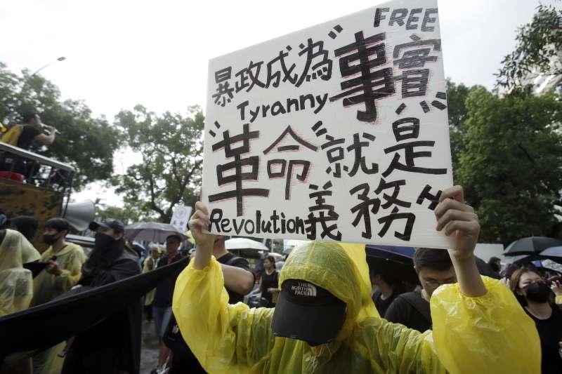 2019年9月29日,香港反送中,「全球連線、共抗極權」大遊行,示威者高舉標語牌「暴政成為事實,革命就是義務」(AP)