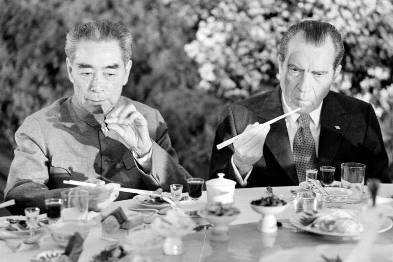 美國總統尼克森1972年2月到訪上海,拿著筷子跟周恩來一起用餐。尼克森也是第一位到訪共產中國的美國總統。(美聯社)