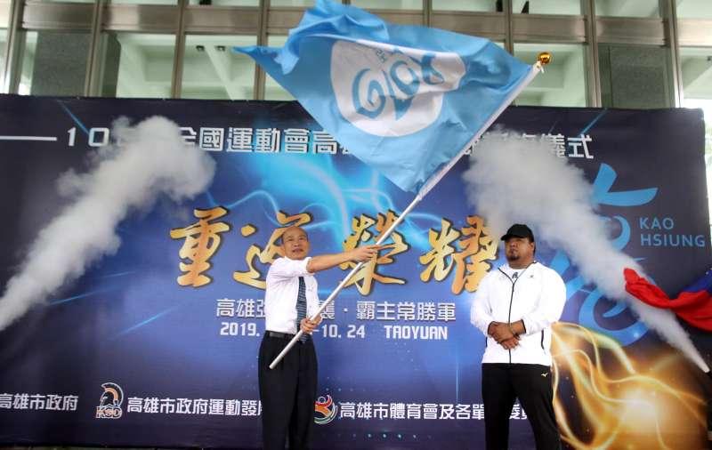 韓國瑜(左)將市旗授予選手代表舉重陳士杰(右)。(圖/徐炳文攝)