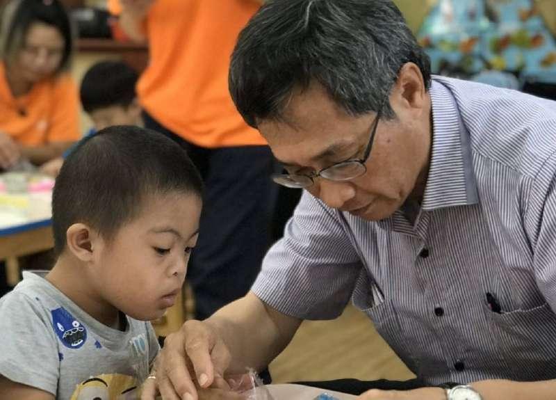 陳國棟(右)與林園早療服務據點的小朋友一起互動玩勞作。(圖/徐炳文攝)