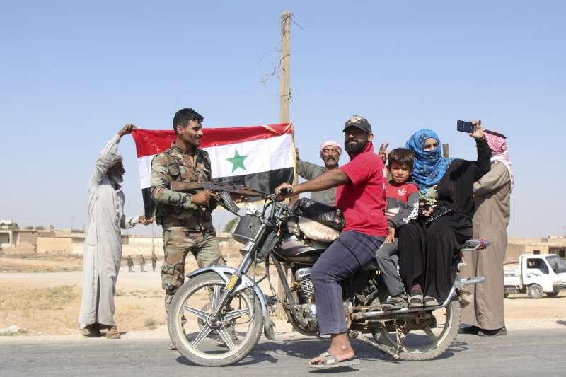 敘利亞政府軍駛入東北地區,援助庫德軍抵抗土耳其入侵,受到當地庫德人民熱烈歡迎。(AP)