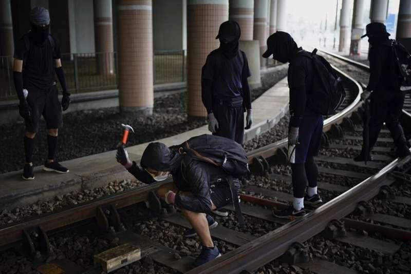 香港的「反送中」抗爭者正在破壞鐵軌。(美聯社)