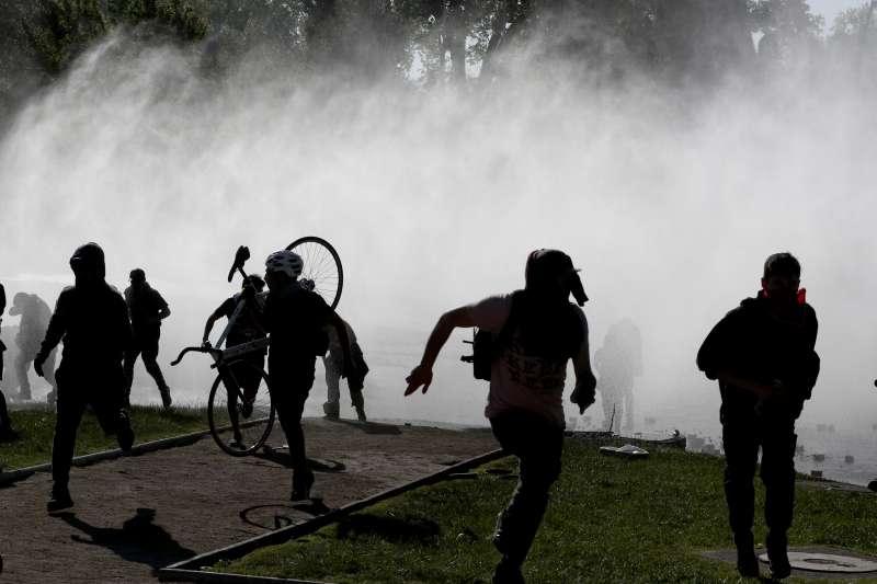 智利連日爆發大規模抗爭,警方施放催淚瓦斯,示威者四處逃竄。(AP)