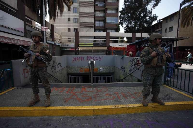 智利連日爆發大規模抗爭,軍方鎮守在遭破壞的地鐵站前。(AP)