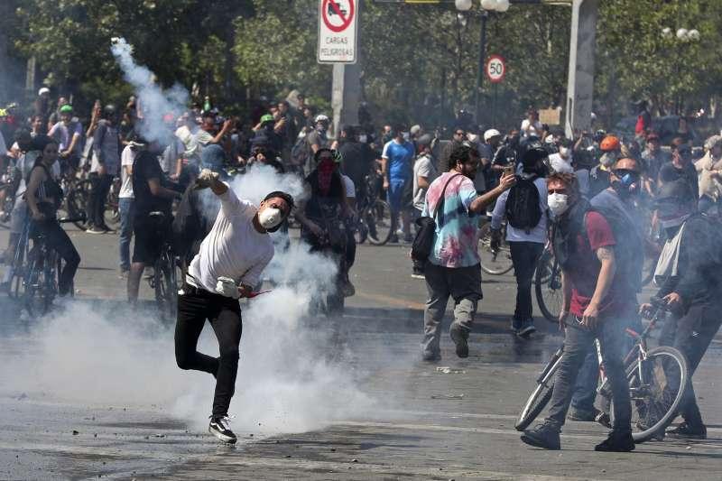 智利爆發大規模抗爭,示威者將催淚瓦斯擲回警方位置。(AP)