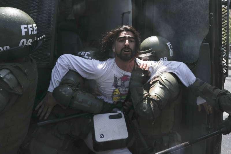智利爆發大規模抗爭,示威者遭警方制伏。(AP)