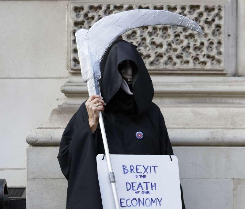 英國一名反脫歐人士扮裝成死神,身上標語寫著「脫歐就是本國經濟的死神」。(AP)