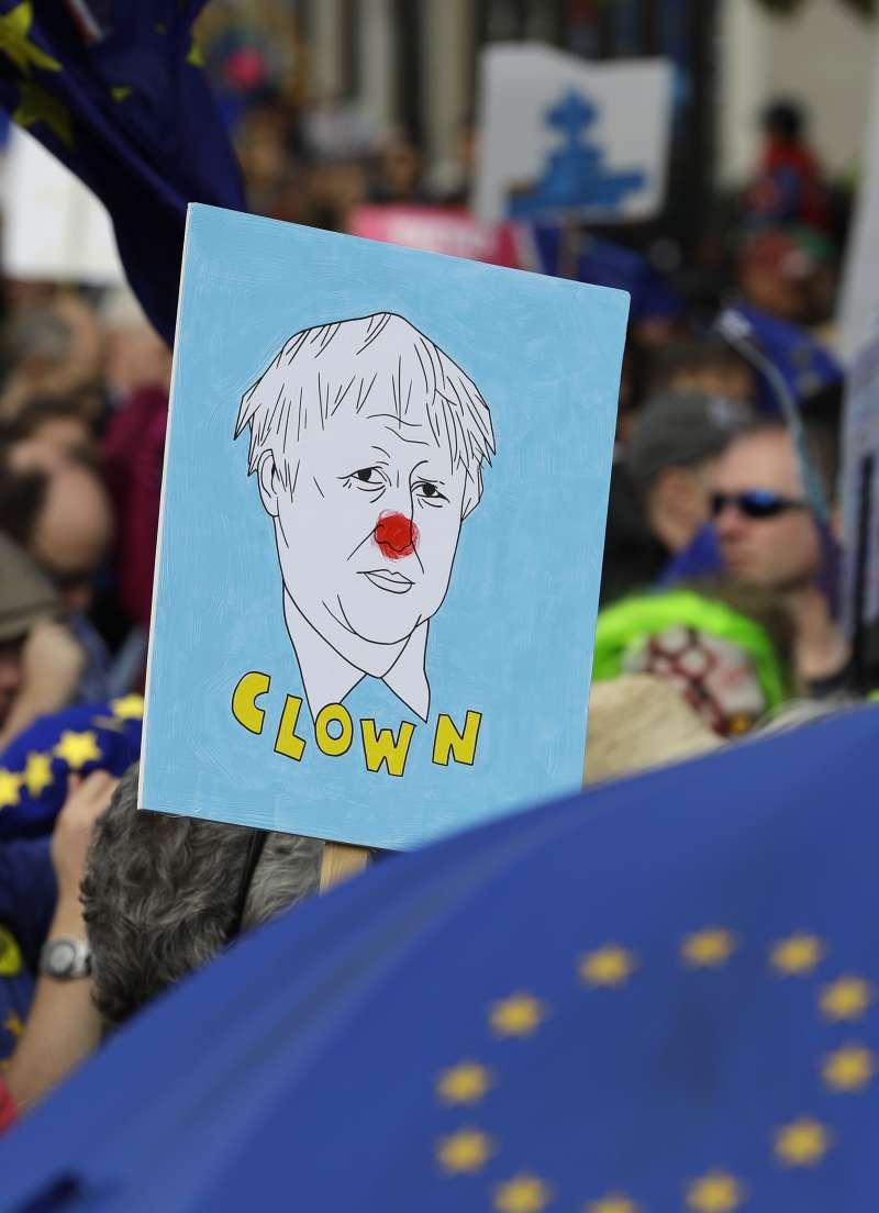 英國首相強森被反脫歐人士畫成小丑。(AP)