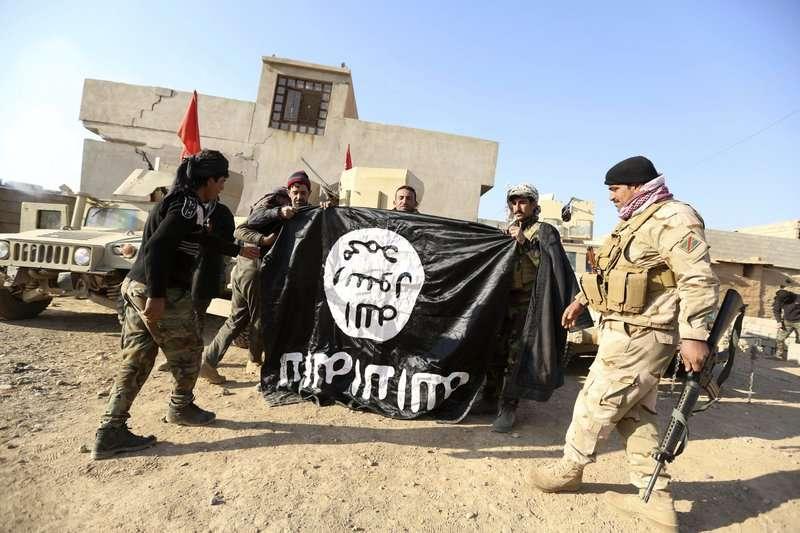 伊拉克士兵奪回摩蘇爾後撤下伊斯蘭國旗幟。(AP)