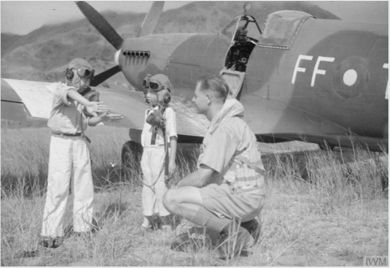 二戰結束後,進駐香港啟德機場的英國皇家空軍132中隊飛行員正在向兩位中國孩童介紹噴火式戰鬥機。此刻的噴火式戰鬥機,仍被中共界定為「中國人民的好朋友」。(照片來源:帝國戰爭博物館)