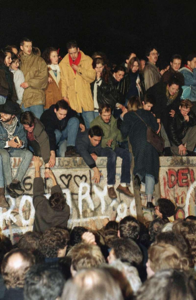 1989年11月10日,西德民眾幫助東德人民爬上分隔城市的柏林圍牆。(AP)