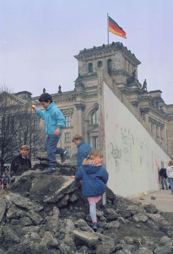 1990年,東西德正式統一,孩童在柏林圍牆的殘跡上玩耍。(AP)