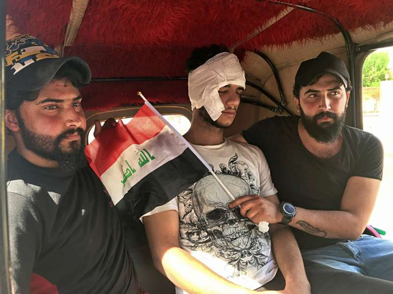 伊拉克示威潮持續月餘,一位受傷民眾坐上免費「嘟嘟車」(Tuk Tuk)前往醫院。(AP)