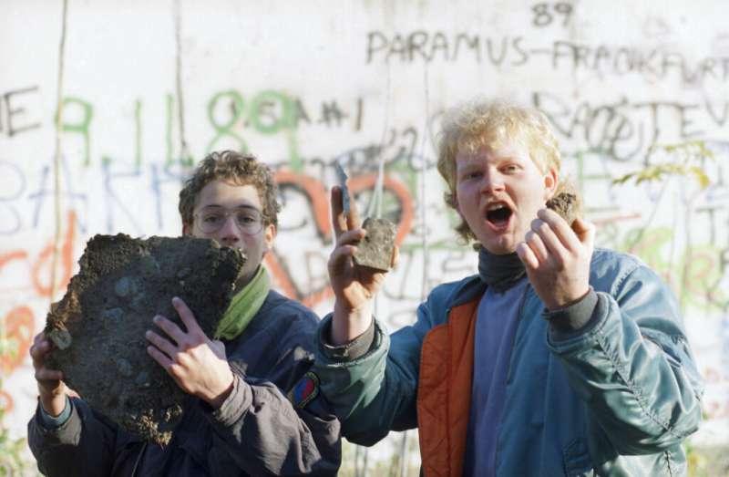 在1989年11月10日的這張檔案照片中,男生自豪地炫耀了他們在柏林布蘭登堡門附近發現的柏林圍牆磚頭。(AP)