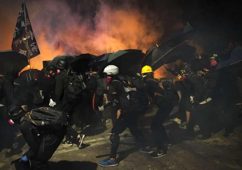 香港抗爭學生12日在中文大學以汽油彈跟路障對抗試圖衝進校園的香港警察。(美聯社)