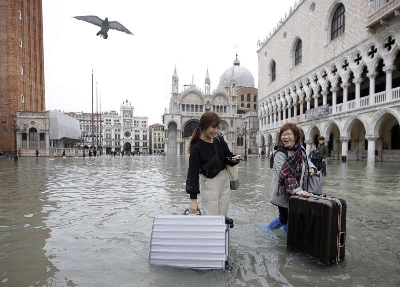 威尼斯近日遭遇洪水,遊客拉著行李箱涉水前進(美聯社)