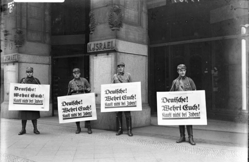 20191115-1933年4月1日,納粹衝鋒隊號召國家抵制猶太商貨。這些部隊在柏林的猶太人開的百貨商店前聚集,標牌上寫道:「德國人!為自己抗爭!不要從猶太人那裡買東西。(作者提供,取自《維基百科》之「猶太人大屠殺」))