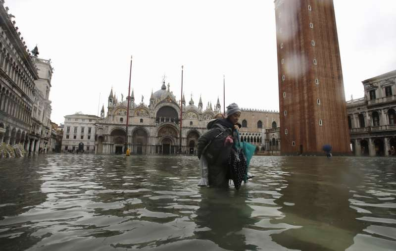 義大利威尼斯近日發生嚴重水災,一名女子揹著女兒涉水走過聖馬可廣場(美聯社)