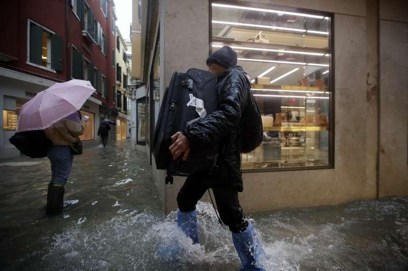 義大利威尼斯近日發生嚴重水災,一名男性遊客抱著行李箱涉水走過街道(美聯社)