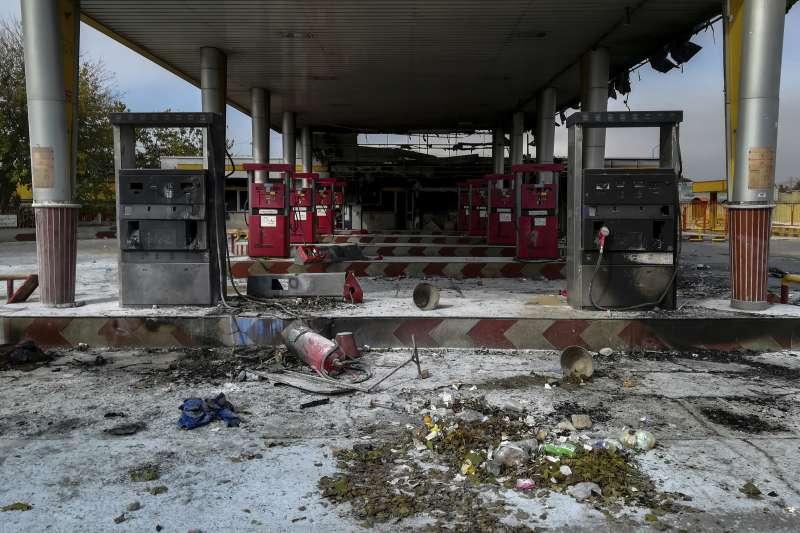 伊朗政府宣布調漲油價,在全國各地引爆激烈抗議,加油站遭示威者焚毀。(AP)